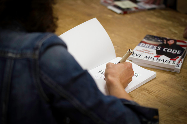 "Author Eve Michaels signs her book ""Dress Code: Ending Fashion Anarchy."""